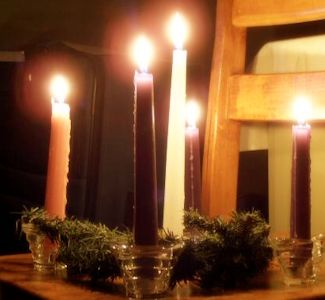 Advent wreath lit and sitting on a wooden chair